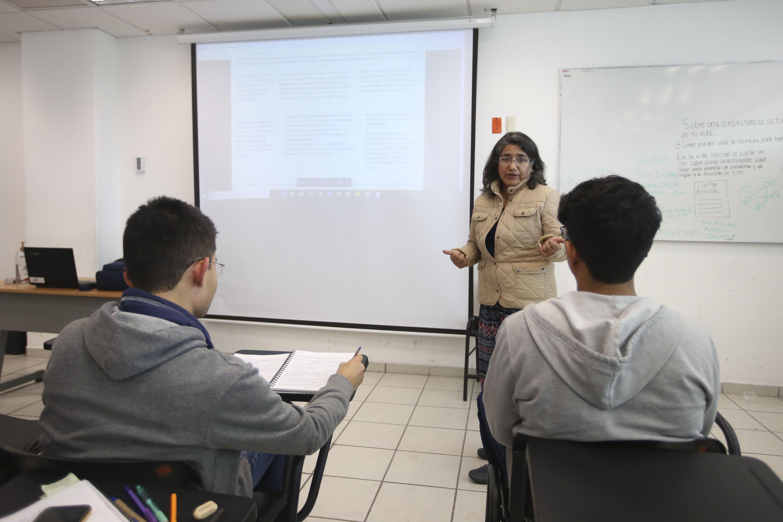 Profesora impartiendo clases e interactuando con sus alumnos.