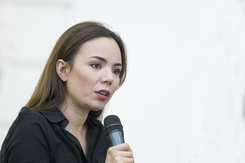 Invitada participante, con micrófono en mano, haciendo uso de la palabra.
