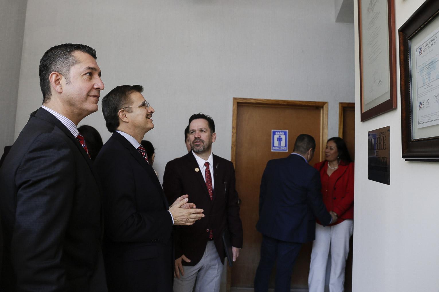 El rector de CULAGOS mostrando al maestro Bravo Padilla los reconocimientos obtenidos en el año