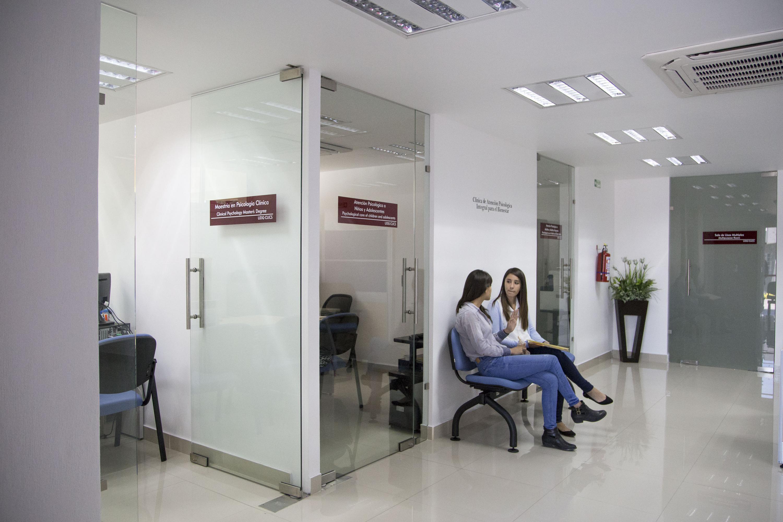Par de mujeres jóvenes, sentadas en un área de espera de un centro de atención psicológica en plantel universitario.