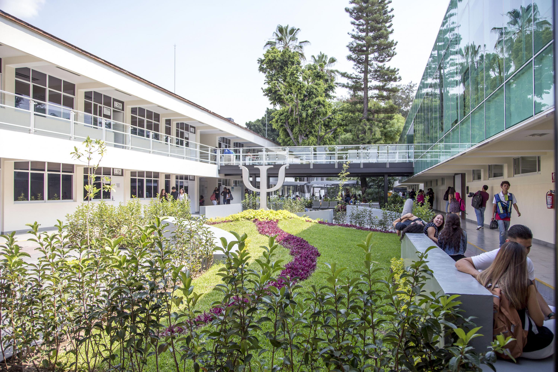 Vista desde el jardín del CAPIB, se ven varios estudiantes sentados en bancas conversando