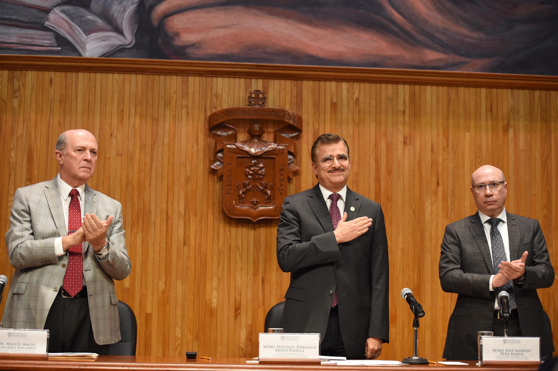 Rector General, maestro Itzcóatl Tonatiuh Bravo Padilla, de pie agradeciendo con mano en el pecho al Consejo General Universitario.Y aun lado de él el Vicerrector Ejecutivo y el Secretario General, de pie aplaudiendo; al final de la Sesión extraordinaria.