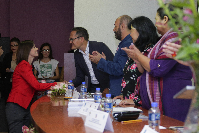 Autoridades de la ceremonia, congratulando a una investigadora y haciendo entrega de un reconocimiento.