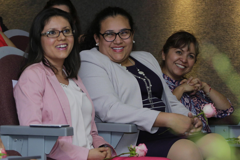 Mujeres de la audiencia, sonriendo, en el evento de reconocimiento.