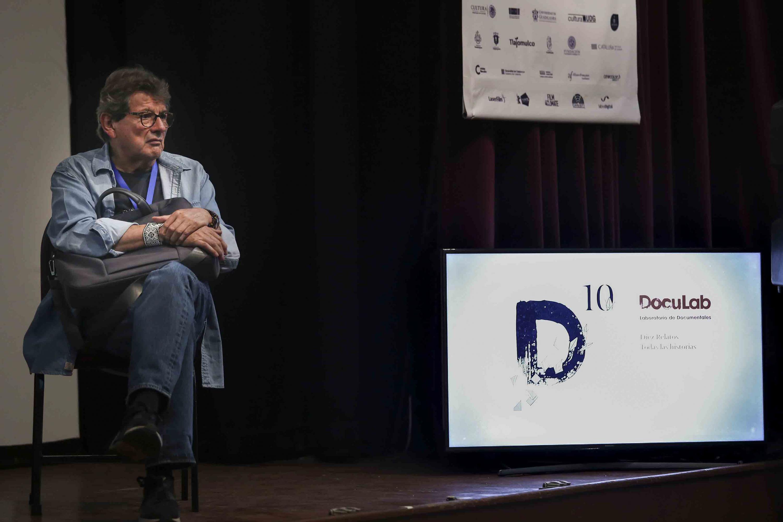 Miembro del presídium sentado al lado de los promocionales del evento.