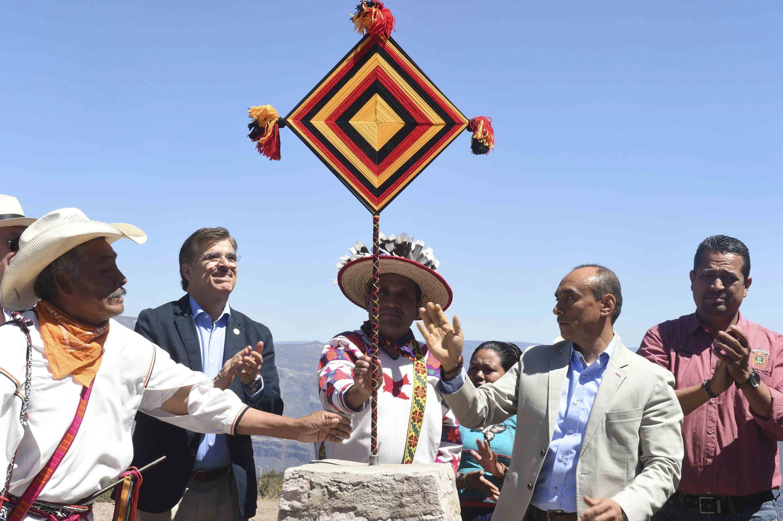 """Autoridades de la Universidad de Guadalajara y de la comunidad Wixárika, colocando la obra plástica """"Ojo de Dios"""" sobre una piedra."""