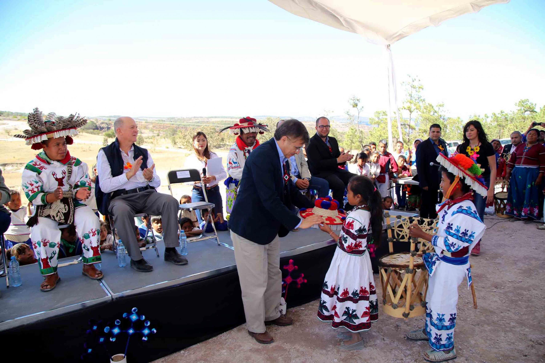 Maestro Tonatiuh Bravo Padilla, Rector General de la Universidad de Guadalajara, recibiendo sombrero conmemorativo de manos de una niña de la comunidad, durante la ceremonia.