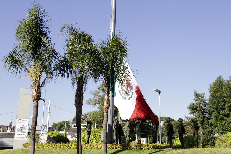 Militares izan la bandera que estará en la fachada del Edificio de rectoria General de la UDG