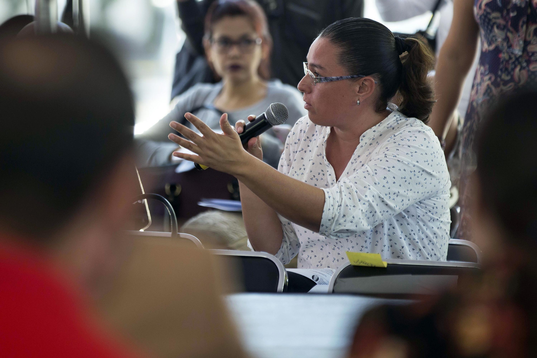 Una mujer del publico hace una pregunta a los presentadores
