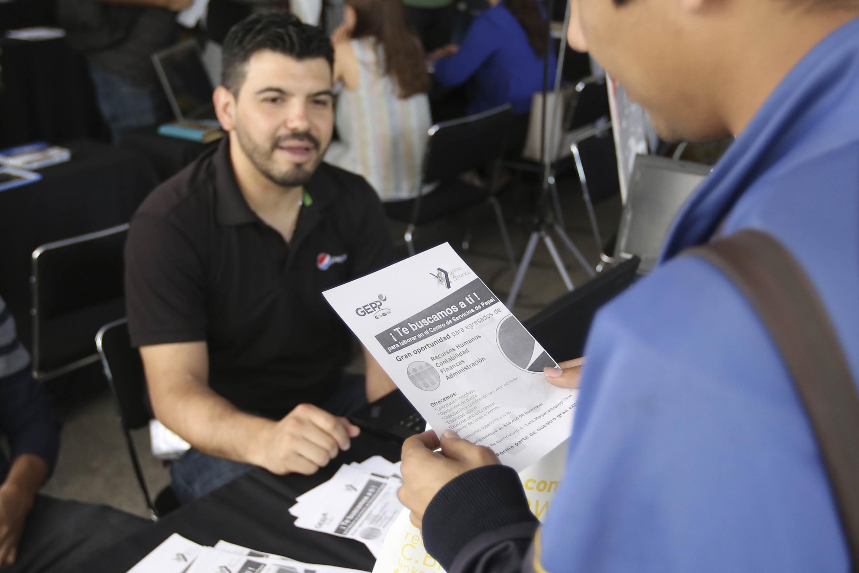 Un joven leyendo un volante con una oferta de empleo
