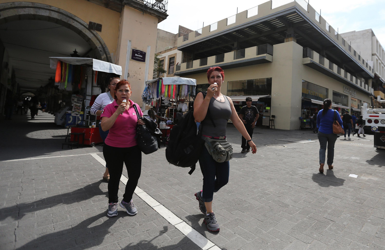 Dos mujeres caminando por el Centro de Guadalajara y comiéndose un helado.