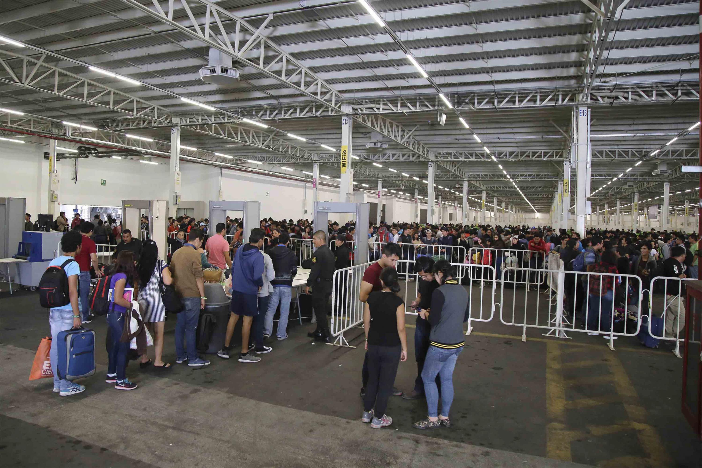 Asistentes al evento haciendo fila y cruzando la zona de seguridad del recinto.