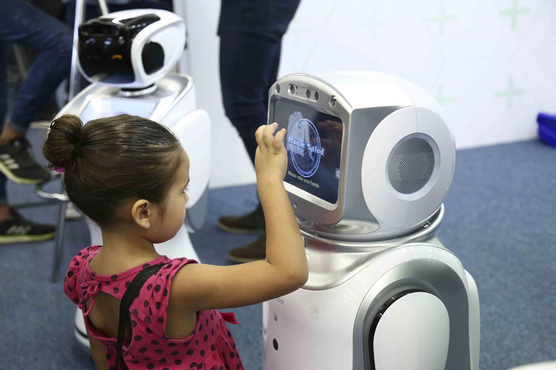 Niña pequeña interactuando con robot durante evento del Talent Land.