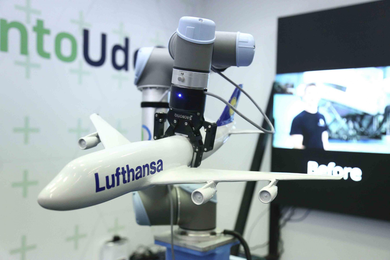 Prototipo de brazo de robot, sujetando en avión em escala.