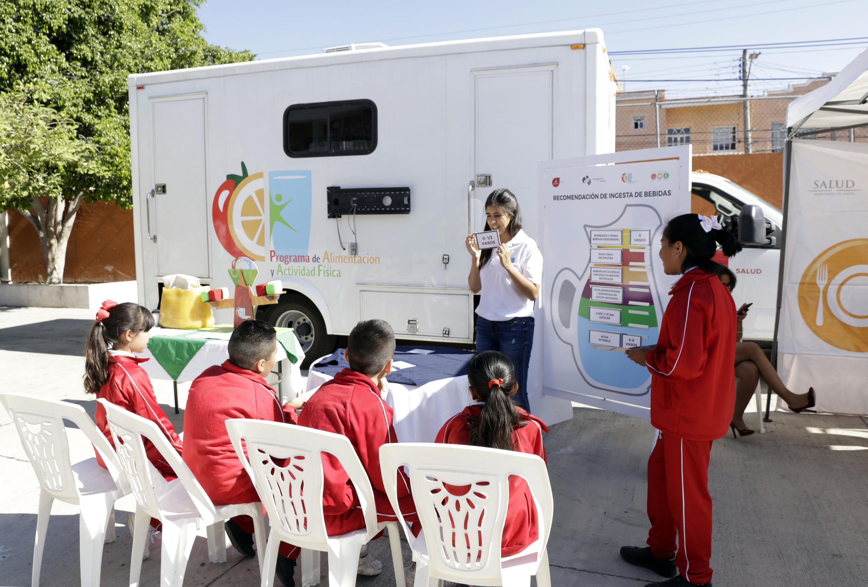 Educadora enseñando a los niños de primaria durante la Semana por el Día Mundial de la Actividad Física