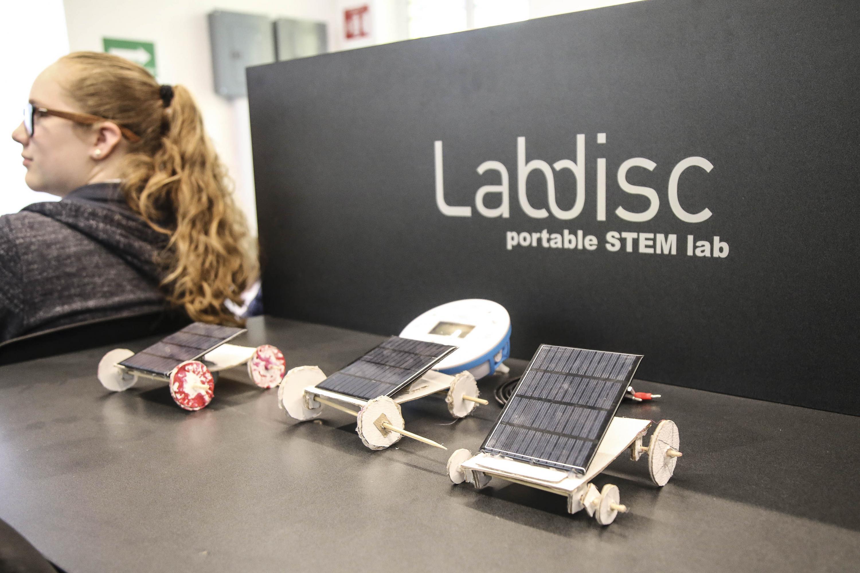 Tres robots pequeños que tienen ruedas de cartón y una placa de energia solar