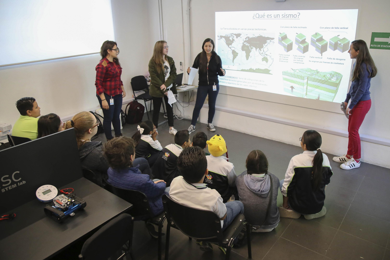 Una joven expositora se dirige al grupo de niños que la escuchan con atención
