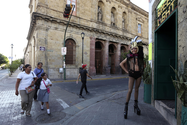 Hombre con  peluca y maquillado como vedette, portando un penacho en la cabeza; posando en las afueras de un local del centro de la ciudad, mientras trausentes pasan cruzando las calles a su lado.