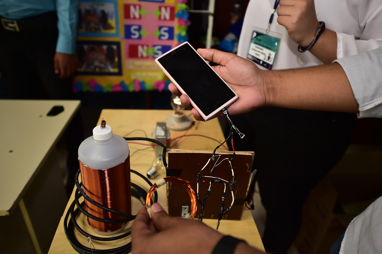 Un estudiante sostiene un smartphone que esta conectado a una bateria que el construyo