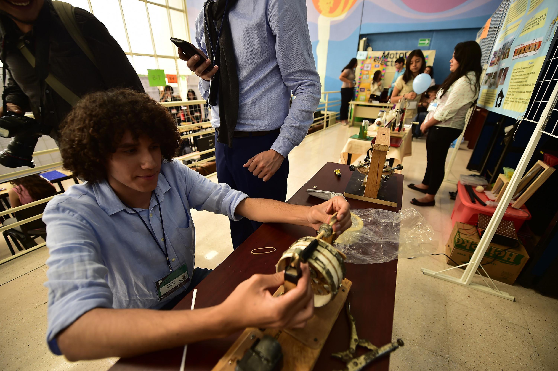 Un estudiante de cabello chino trabaja en la construccion de un motor