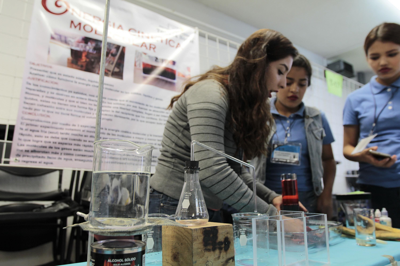 Una bachiller muestra a dos compañeras un experimento de quimica molecular