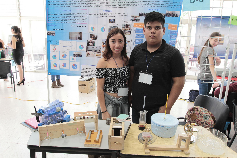 Una pareja de estudiantes posan junto a todos los aparatos y motores de la exhibicion
