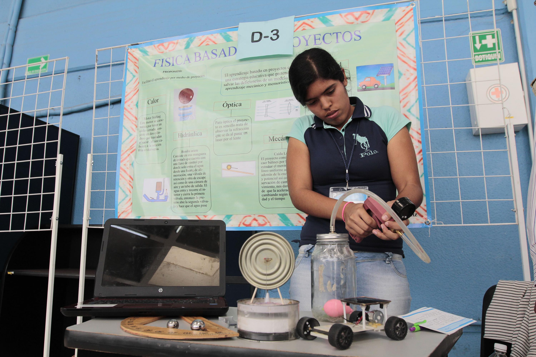 Una estudiante construyendo un aparato con mangueras y un frasco de cristal