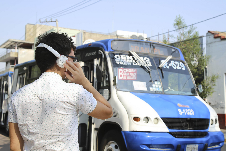 En una calle de la ciudad un joven con audífonos y un camión de transporte publico