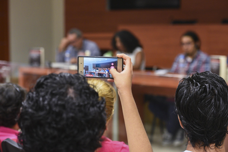 Una asistente toma una fotografía con su telefono inteligente a los presentadores del libro