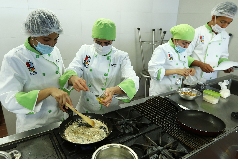 Estudiantes de la Licenciatura en Nutrición del Centro Universitario de Ciencias de la Salud, cocinando en el laboratorio.