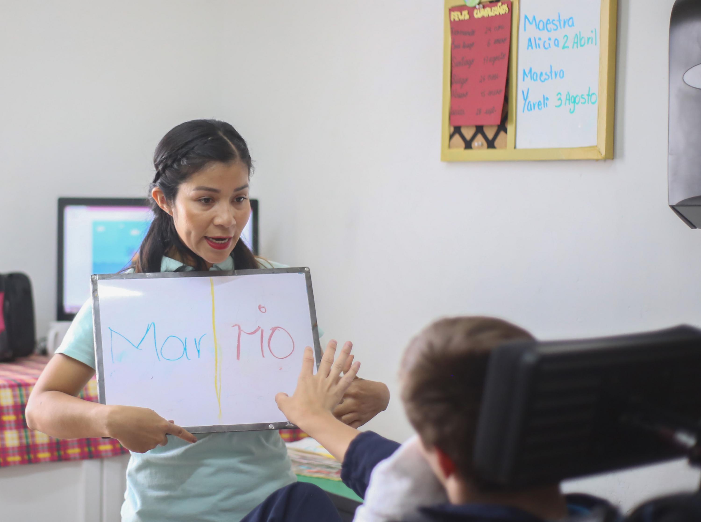 Maestra del centro psicoeducativo, mostrando un pintarrón con palabras para enseñar a un niño.