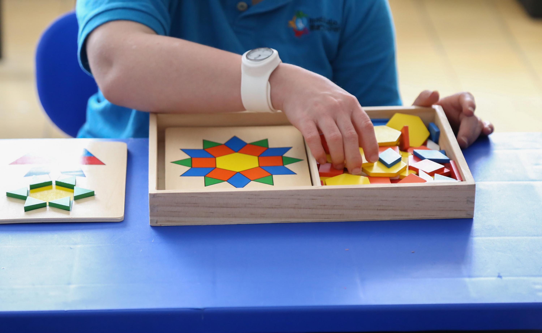 Niño, formando una figura geométrica, con material educativo del centro.