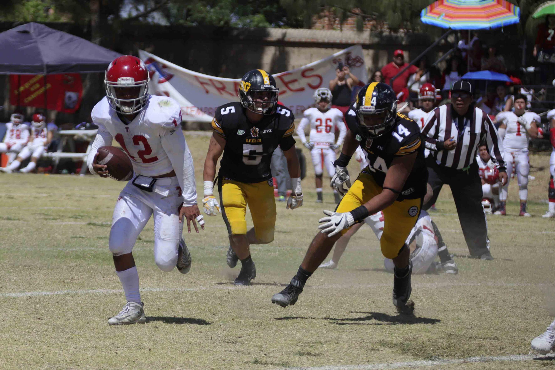 Los jugadores defensivos de la Leones Negros corren detras de un jugador de los Frailes que tiene el balon