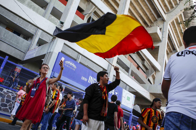 Un aficionado de los Leones Negros agita una bandera a lasa afueras del estadio Jalisco