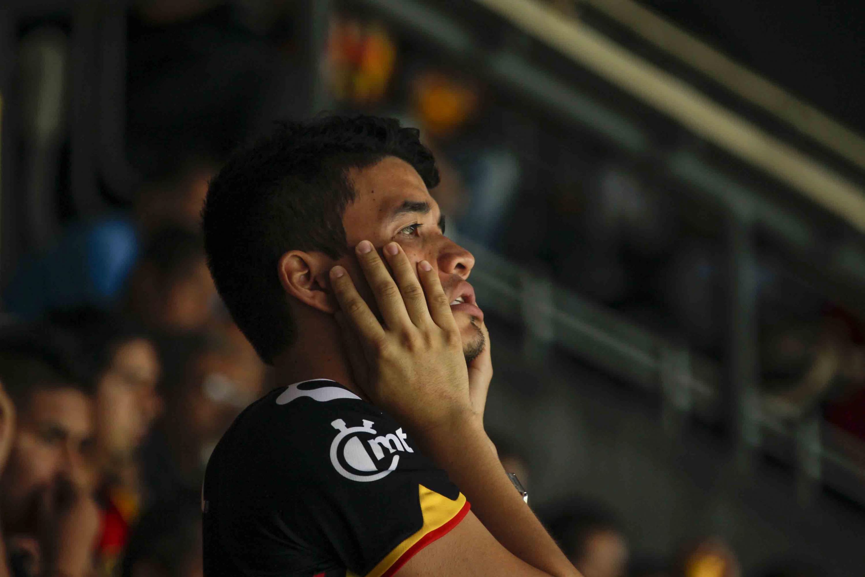 Un aficionado de leones negros viendo el partido de la final de ascenso preocupado y con las manos en la cara