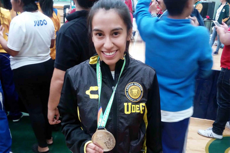 Karla Abigail Salazar Pérez, estudiante del Centro Universitario de Ciencias Económico Administrativas (CUCEA), mostrando su medalla de plata.