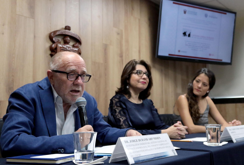 Doctor Jorge Durand, investigador del Centro Universitario de Ciencias Sociales y Humanidades (CUCSH), con micrófono en mano haciendo uso de la voz.