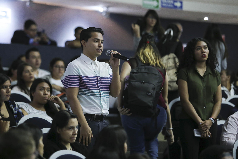 Estudiante del Centro Universitario de Ciencias de la Salud (CUCS) con micrófono en mano, dirigiéndose a los candidatos.