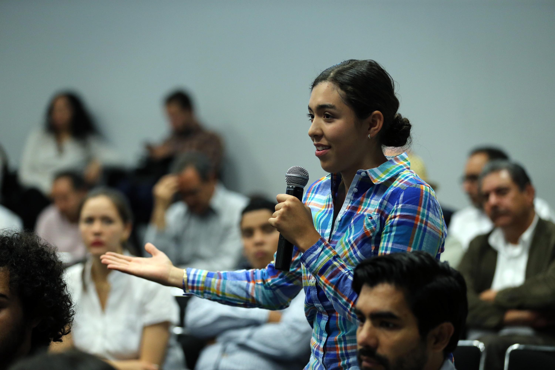 Estudiante de la UdeG, con micrófono en mano, haciendo una pregunta al candidato del PAN a la gubernatura de Jalisco.