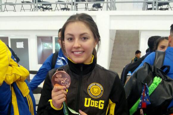 Paola Padilla, deportista de karate kumite y estudiante del Centro Universitario de Ciencias Económico Administrativas (CUCEA), mostrando su medalla de bronce.