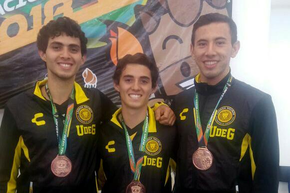 Deportistas de karate en la modalidad de kata y estudiantes de la Universidad de Guadalajara, mostrando sus preseas de bronce.