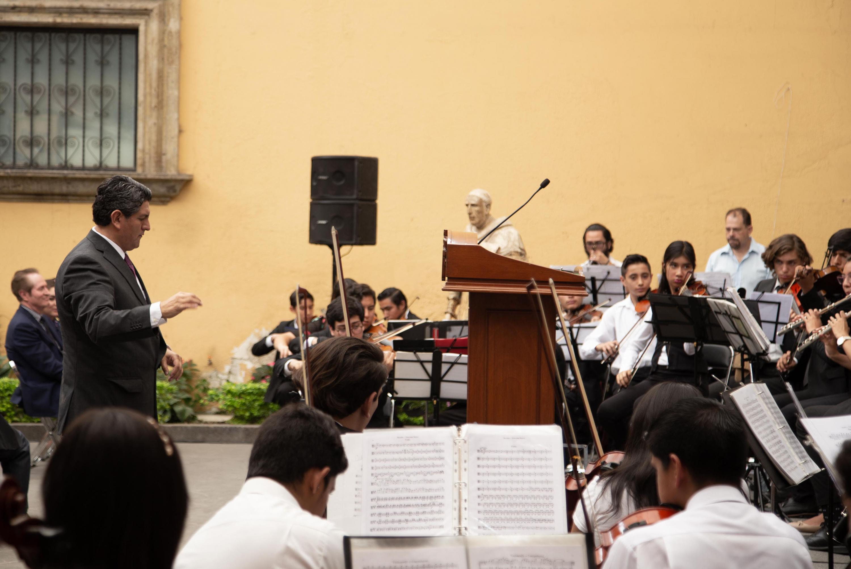 El maestro Marlon Jiménez dirige la orquesta juvenil durante el evento de aniversario