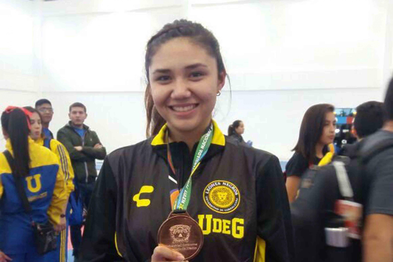 Atleta de la Universidad de Guadalajara, mostrando su medalla de bronce.
