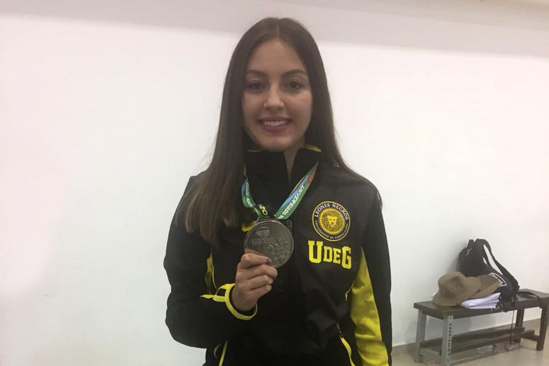 Paola Padilla sonrie mientras enseña la medalla de plata