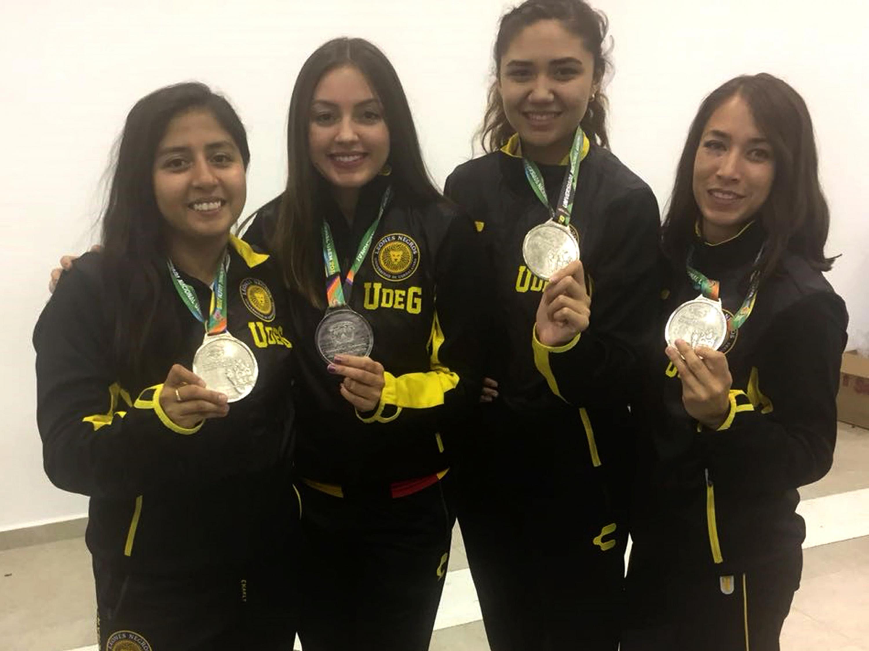 Las cuatro integrantes del equipo de karate de la UDG muestran la medalla obtenida