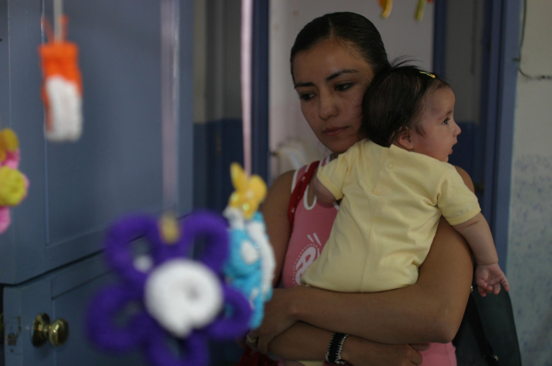Madre cargando a su bebe de pocos meses de nacida y con semblante pensativo.