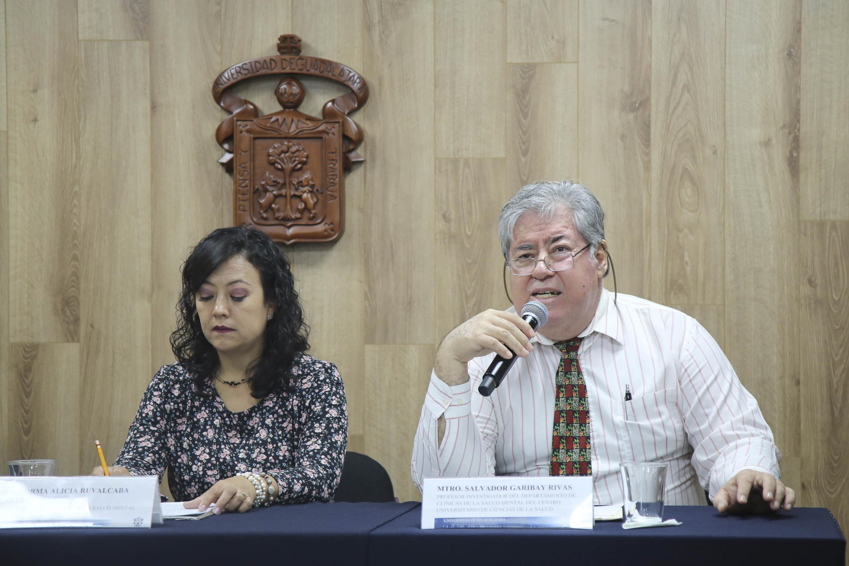 Maestro Salvador Garibay Rivas, profesor investigador del Departamento de Clínicas de la Salud Mental del CUCS, con micrófono en mano haciendo uso de la voz.