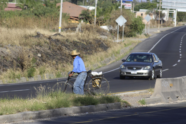 Un hombre espera el paso de un automóvil para cruzar la carretera con su bicicleta