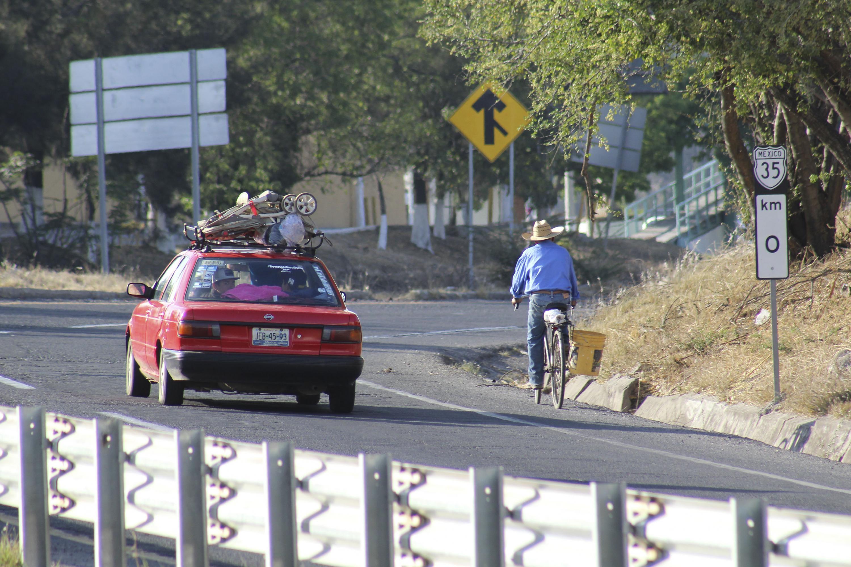 Un hombre conduce su bicicleta en la carretera del entronque de Santa Rosa con La Barca