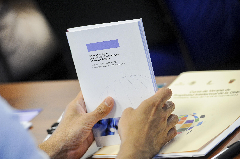 Una persona sostiene en sus manos el Convenio de Berna para la proteccion de las Obras Literarias y Artisticas